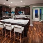 Kitchen With Woode Laminated Floor, Dark Brown Cabinet, Dark Brown Island With White Counter Top, White Chairs, Blue Pendant Lights, One Side Of The Wall Painted Blue.