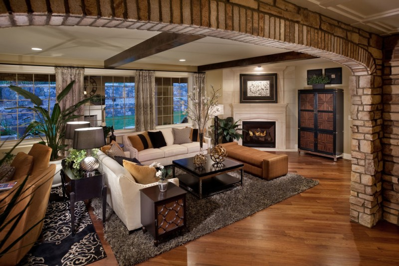 large brick arch way grey rug white sofa brown sofa dark hardwood floor square wooden coffee table fire place
