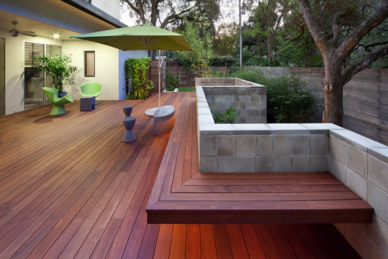 large contemporary deck with modern outdoor furniture concrete block railings and dark wood siding floors