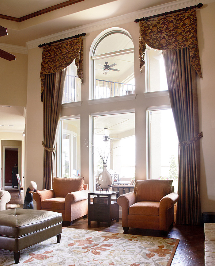 large dark brown half window curtains with black wrought iron rods leather ottoman chair orange arm chairs modern rug with floral motifs