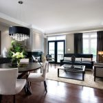 Livign Room In Condo With Dark Wood Floor, White Chairs With Dark Wood Table, Brown Rug, Brown Sofas, Black Sofa, Glass Coffee Table, Brown Curtain, Round Crystal Chandelier