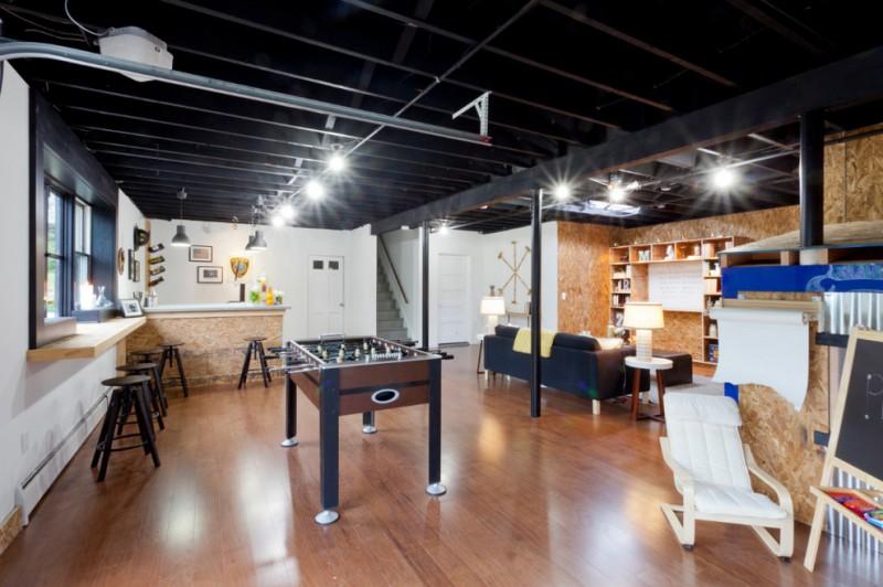 living room basement with bar in one side, foosball, bookshelves, black sofa