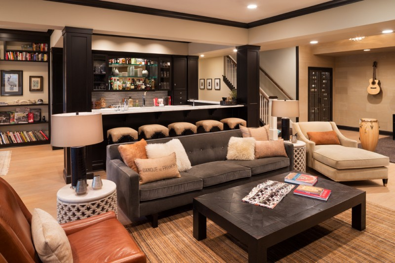 living room basement with grey, brown, beige sofa and couches, and bars, with side table, white table lamp, bookshelves