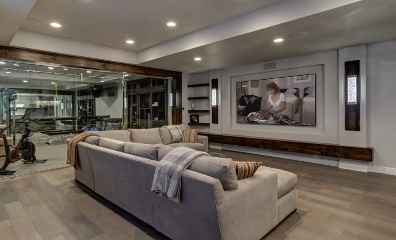 living room basement with hoem theater and beige sofa and gym