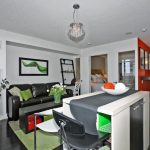 Living Room In A Condo With Dark Wood Floor, Dark Brown Leathered Sofa, Black Wooden Coffee Table, Black And White High Chairs, Green Rug, Green Pillows, Open Kitchen With Green Small Rug