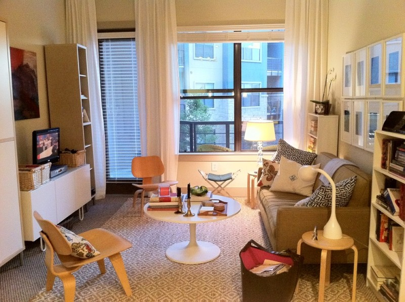 living room in a condo with rug, wooden chair, brown sofa, brown cabinet, brown and white shelves, brown sofa, table lamp, reading table lamp white curtain