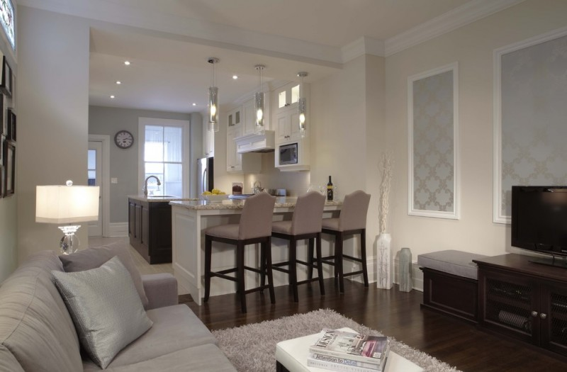 living room with grey sofa, gey rug, wood cabinet, wood floor, and open kitchen with brown high chairs, white island, brown cabinet, white walls
