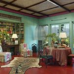 Living Room With Safari Decor Tiger Rug, Plants, Wooden Chair, Couchm Green Wall