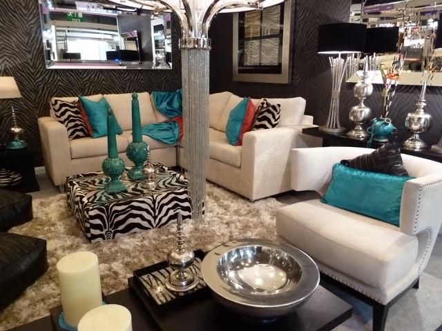 living room with white fur rug, white sofa, zebra pattern ottoman for table, zebra pattern pillow, chandelier