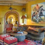 Living Room With Yellow Wall, Indian Painting, Animal Miniature, Boar Head Wall Mount, Red Ottoman, Greysofa With Orange Pillows
