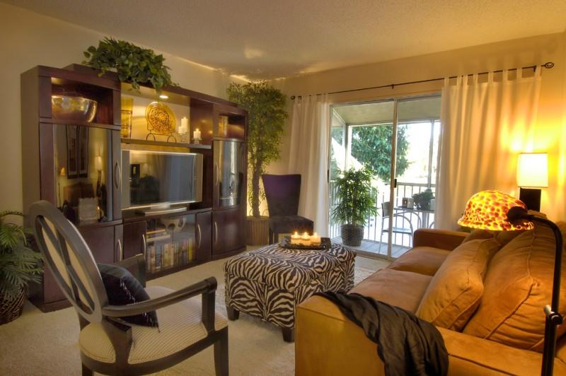 living room with zebra patter ottoman, giraffe pattern floor lamp, wooden entertainment cabinet, brown sofa