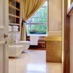 Luxurious And Glamorous Bathroom With Pale Gold Curtain White Toilet White Ceramic Floors Wooden Vanity With Glowing Gold Line Accent Recessed Shelves For Storage