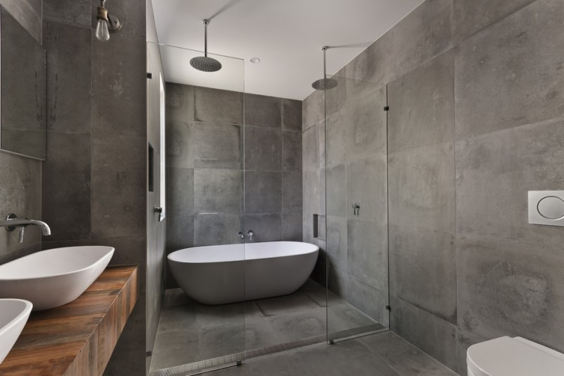 luxurious bathroom design with concrete tiles for floors and walls white bathtub glass partitions wood top bathroom vanity double free standing vessel sinks toilet