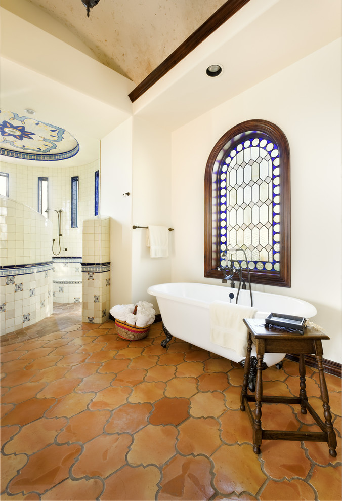 mediterranean bathroom idea with exotic terra cotta floors white walls white ceramic tiles for shower's walls and floors white free standing bathtub small table