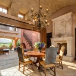 Mediterranean Dining Room With Wrought Iron Chandelier, Wooden Table Set, Sand Color On Ceiling, Stone Floor, Wall, Fireplace