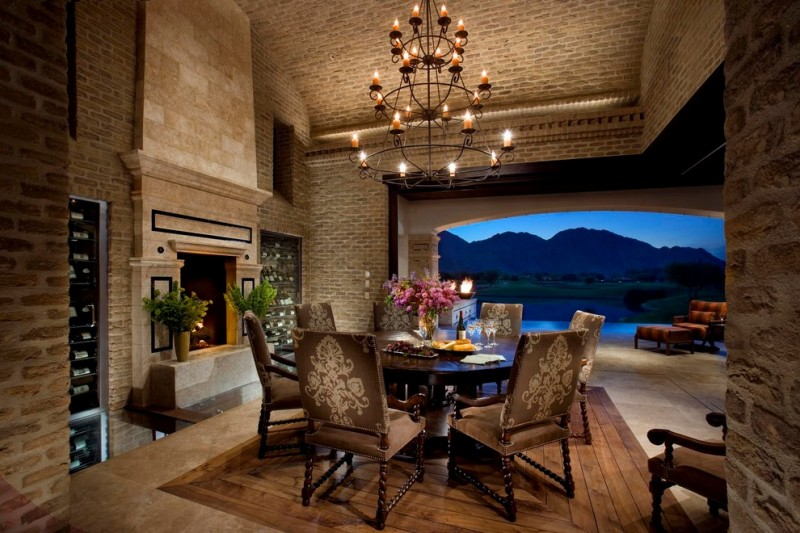 mediterranean dining space with sand color wall and ceiling, wooden floor, wrought iron chendelier,
