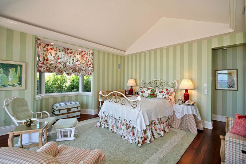 mediterranen coastal bedroom design with flower motifs half curtain a bed set with classic metal headboard and feetboard classic chair with side table deep light green stripes walls