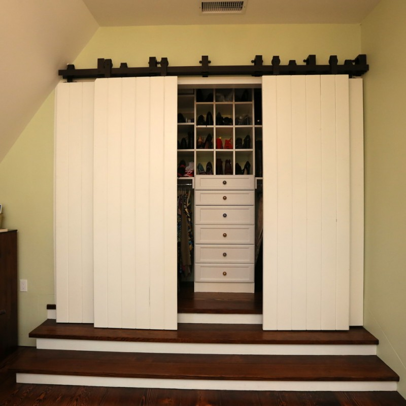 mid sized walk in closet organizer idea with white interior barn door and low staircase additions