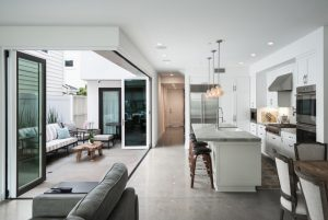 modern open kitchen with grey flooring grey countertop, white wall, white counter, pendant lights, bi fold door to patio