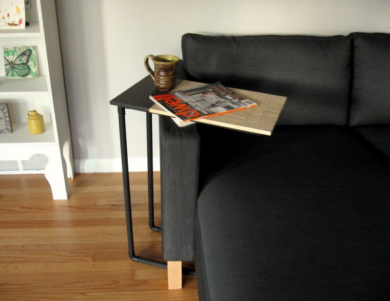 moveable side table with black thin legs and black brown wooden top