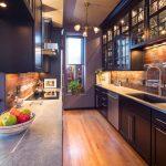 Narrow Transitional Kitchen Design Dark Purple Cabinets Dark Purple Shaker Cabinets Stainless Steel Appliances Red Bricks Backsplash Medium Toned Wood Floors Grey Countertop