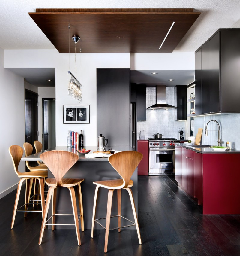 open kitchen in condo with dark wood floor, grey island, brown wooden chairs, red and black cabinet, white wall