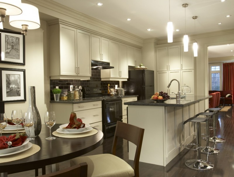 open kitchen with white ceiling, wall, cabinet, black counter top, dark wooden dining set, pendant lights,