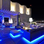Outdoor Seating Space With LED Lighting Under The Furniture, The Branch, And White Floor Lamp Beside The Sofa
