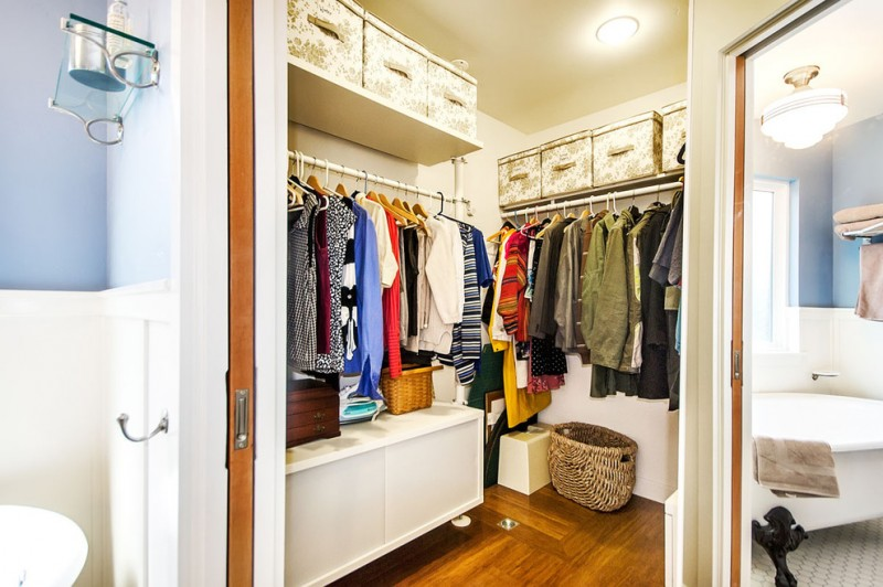 pocket door with small walk in closet dark wood floors some basket storage