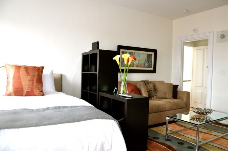 queen size bed with white cover, parted with book shelves