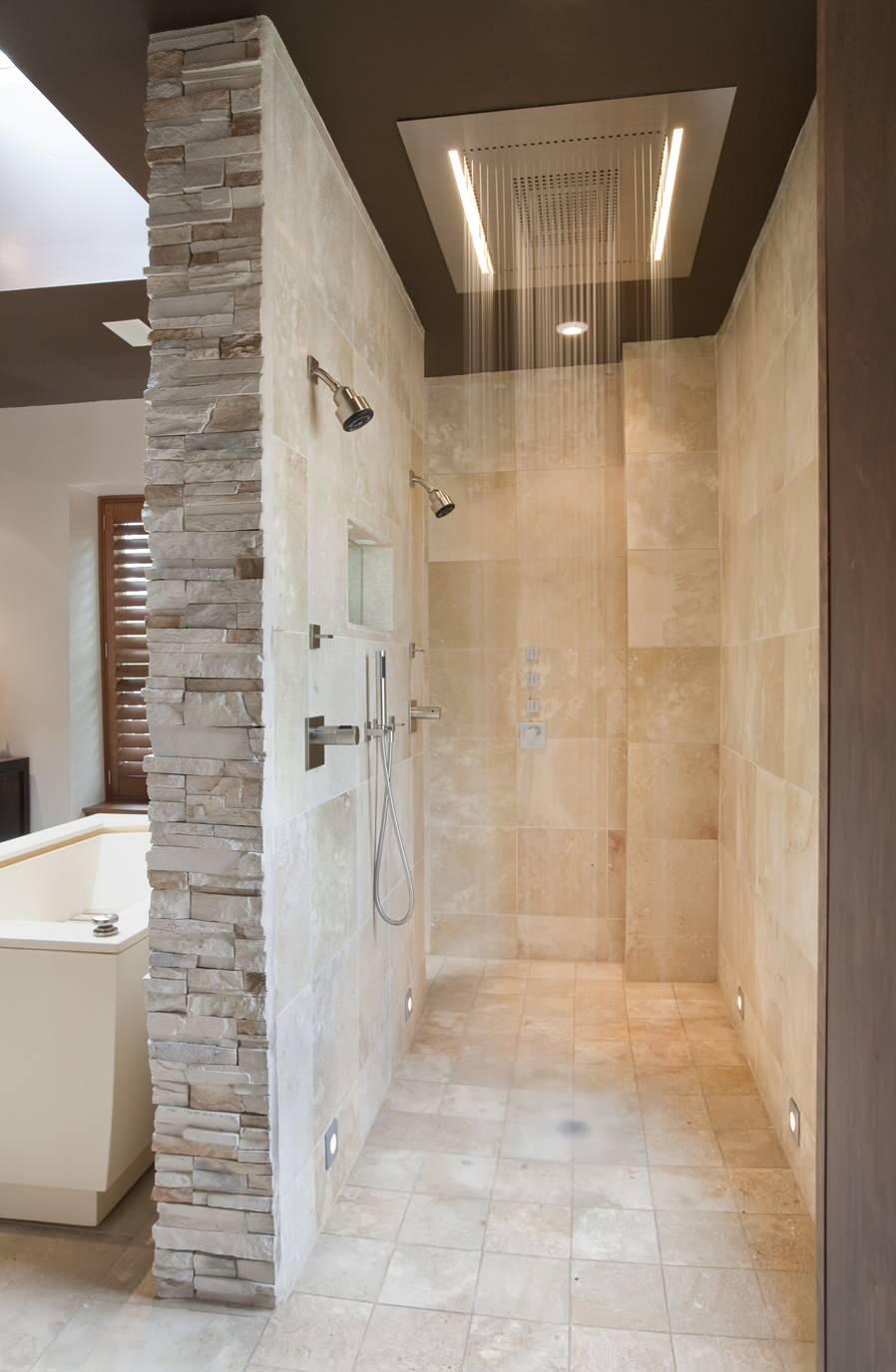 rain head shower beige wall stone tiled wall dark colored ceiling walk in shower space marble floor