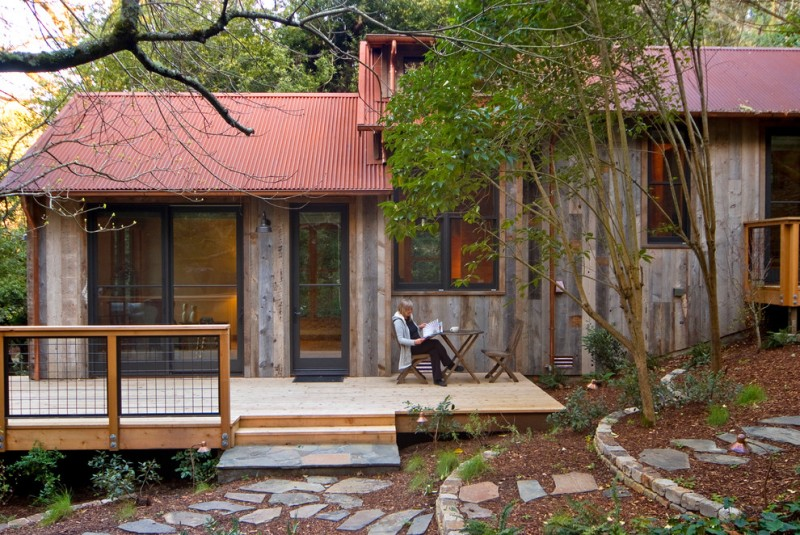 raw rustic guess cabin exterior with full glass windows and door modern lightweight railing system with wood frame red and lightweight metal roofs