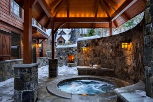 rustic built in ground hot tub with tall stone wall and cedar wood ceiling
