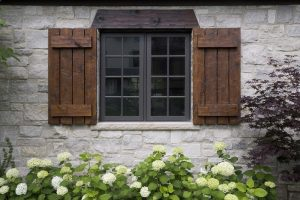 rustic exterior idea with stone walls and hand made window shutters and header