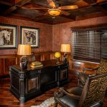 Rustic Office With Wooden Flooring, Half Down Wooden Wall, Wooden Table, Brown Lamps, Brown Lamp Fan, Brown Leather Chairs With Zebra Skin Motives In The Back