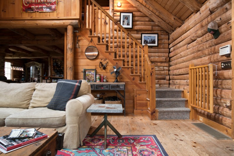 rustic staircase model with exotic logs and timbers cozy sofa multicolor rug with motifs grey top side table