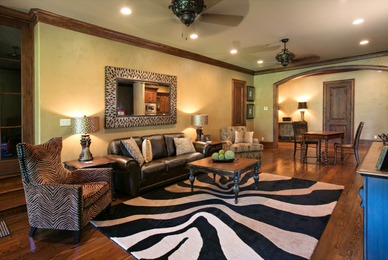 safari theme living room with zebra pattern rug, zebra pattern couch, zebra pattern lamp, zebra pattern window frame, black sofa, zebra pattern pillos, wooden coffee table