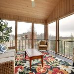 Screen Porch With Black Metal Railings Cozy Porch Furniture Some Accent Pillows Rug With Floral Motifs And Ceiling Fan With Center Lamp