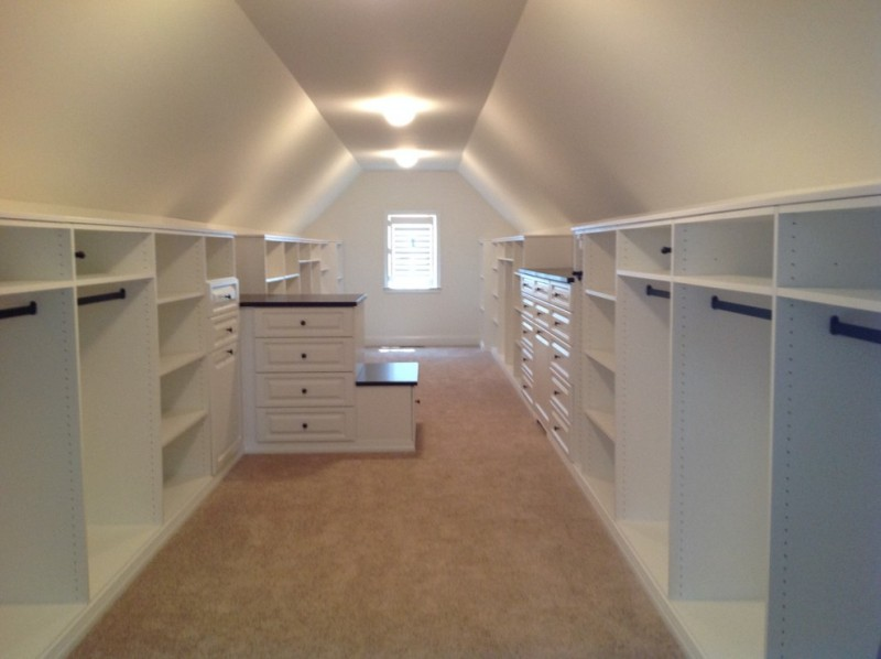 simple and minimalist walk in closet in vaulted roof room small window with white shutter small center table beige flooring system
