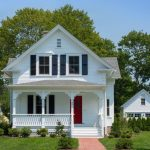 Simple White Farmhouse With White Lattice Railing System Glass Windows And Red Front Entrance Door