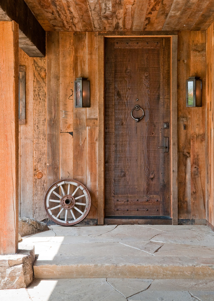 single front door for ranch a decorative wheel a couple of ranh themed wall lamps metaldoor knock