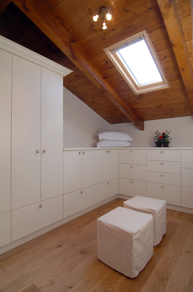 slanted ceiling walk in closet design in clean white light toned wooden floors oak ceiling a pair of white chairs with white slipcovers