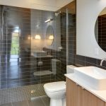 Small Bathroom With Brown Tiles In Shower And Toilet Sink Area, Black Tiles In Shower Wall And Half On The Sink Toilet Area, And White Painted Wall For The Rest, Glass Panel