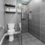 Small Bathroom With Grey Flooring, Grey Tiles In Shower Wall, Grey Painted Wall In White Toilet Area, Glass Panel, Wooden Shelves On Top Of The Toilet