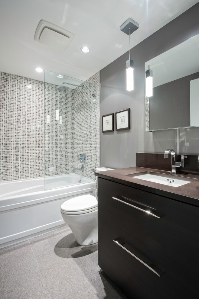 small bathroom with white bathtub, white brown tile in the shower area, grey wall, white toilet, dark brown cabinet with brown top, mirror