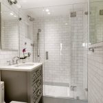 Small Bathroom With White Flooring, White Tradiional Tiles Wall, Toilet, Brown Cabinet Under The White Sinks, Mirror