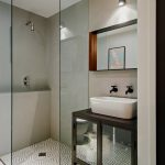 Small Bathroom With White Tiles In Entire Walls, White Pattern Tiles Flooring, White Sink, Wooden With Glass Door Cabinet Under The Sink, Glass Panel On Two Sides, Mirror