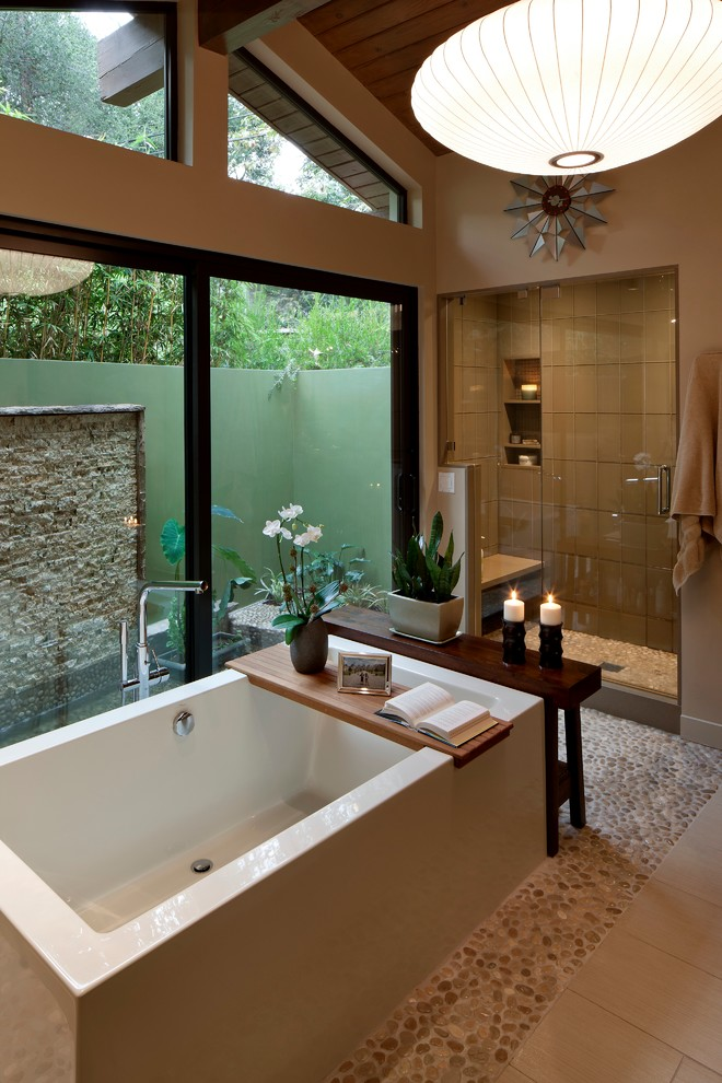 small rock tiles flooring idea rectangular bathtub with wooden panel walk in shower space with beige ceramic tiles walls and small rock tiles floors shower bench recessed shelves