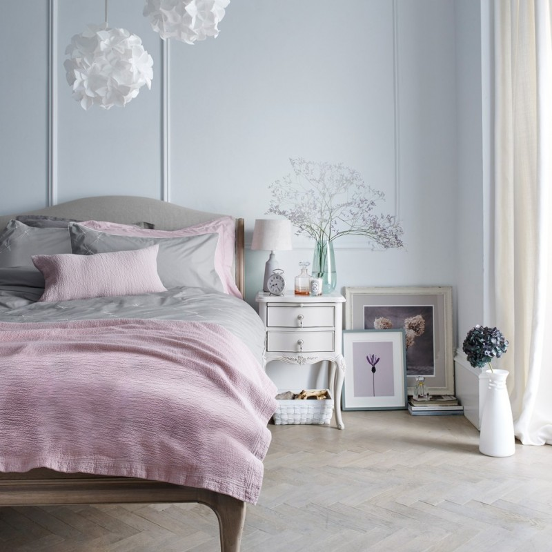 soft grey bed sheet collaborated with soft pink blanket soft pink pillow shams soft grey pillow shams white bedside table white hung decorations