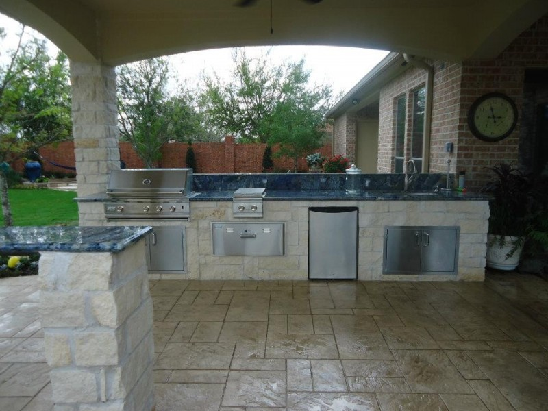 summer kitchen in patio with warm flooring and ceiling, barbeque grill, yellow brown stones under the counter, black counter top